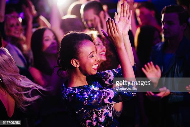 African descent girl enjoys dancing with friends in nigh club