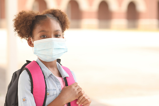 African descent, girl on school campus. Mask for COVID-19. 1251047993