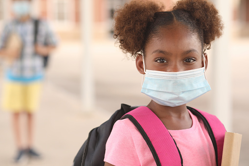 African descent, girl on school campus. Mask for COVID-19. 1251048029