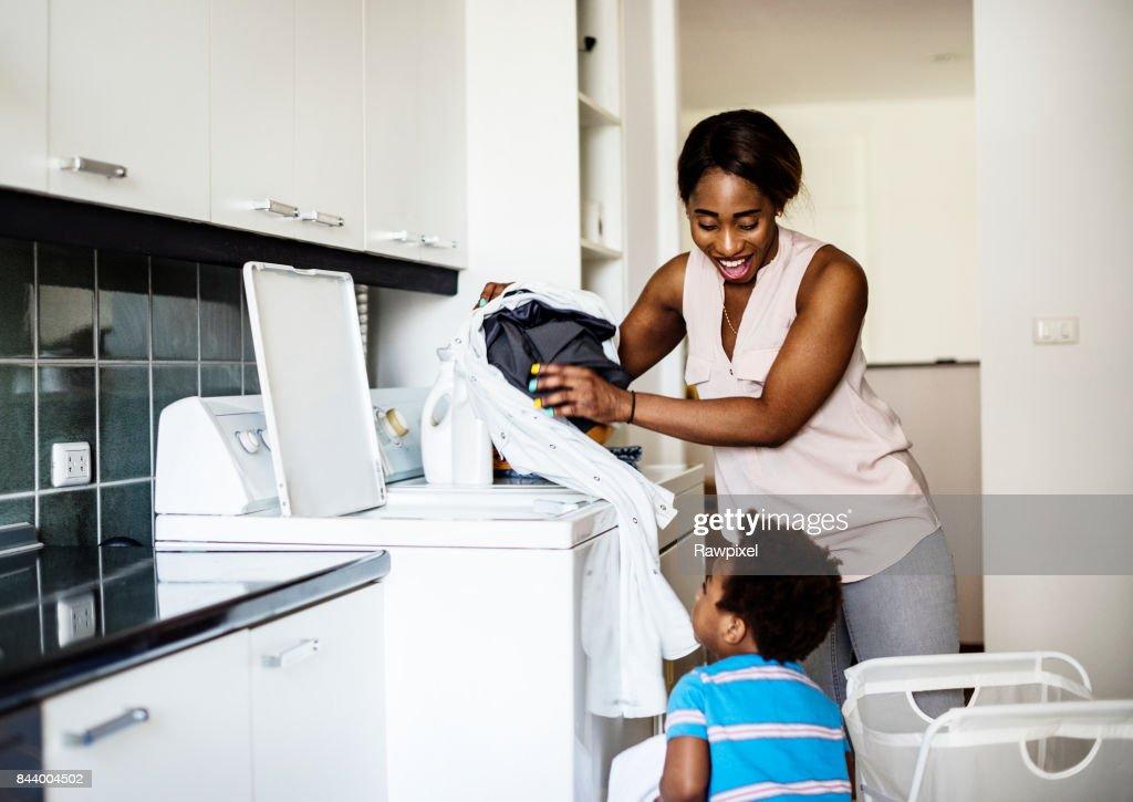 Afrikanischer Abstammung Kind hilft Mutti die Wäsche : Stock-Foto