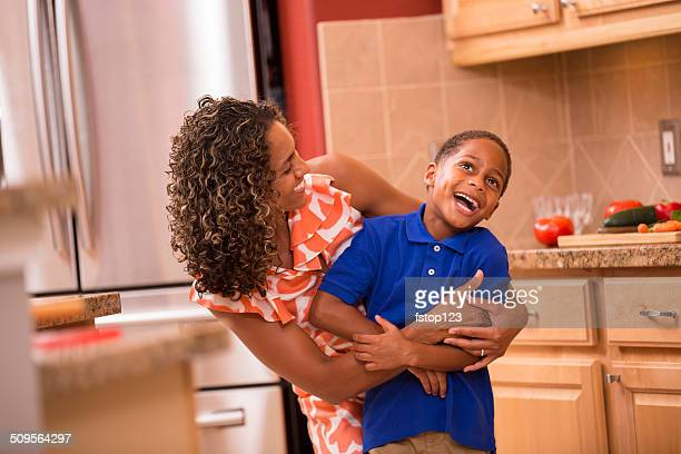 African descent little boy and mother hug, laugh home kitchen.