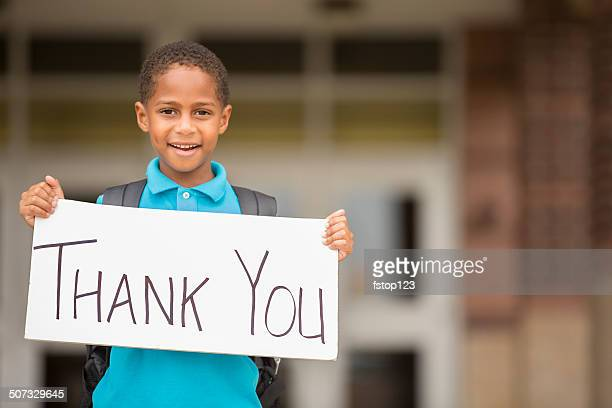 African descent, little boy holds 'thank you' sign. School.