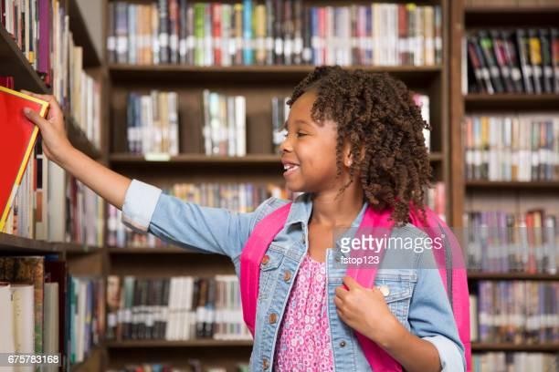 African descent little girl in school library choosing book.