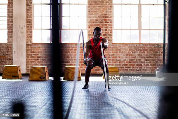 African descent man doing battle rope exercise in cross training