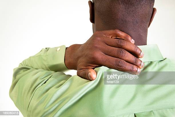 African descent man massaging his neck in pain.