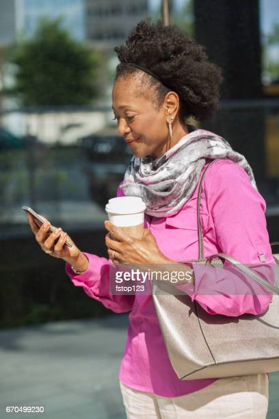 African descent, mature woman with cell phone, coffee in downtown city area.
