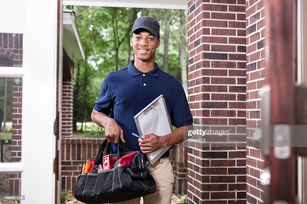 African descent repairman at customer's front door. : Stock Photo