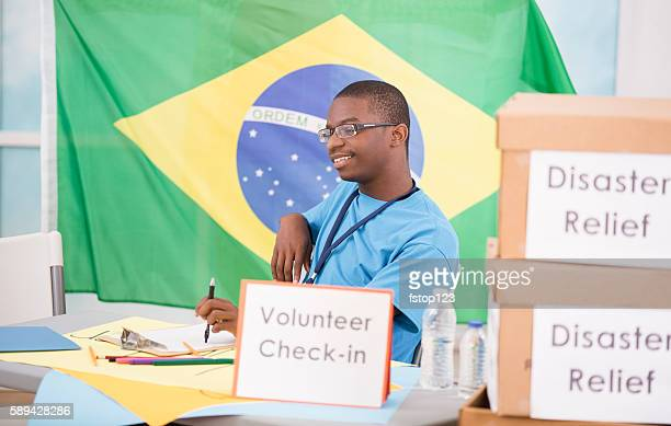 African descent teen boy registers at volunteer check-in table.