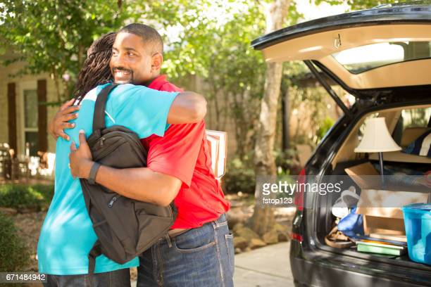 African descent teenage boy packs car to move to college.