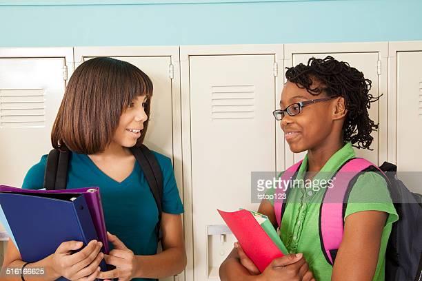 African descent, teenage girl students talk in school hallway. Lockers.
