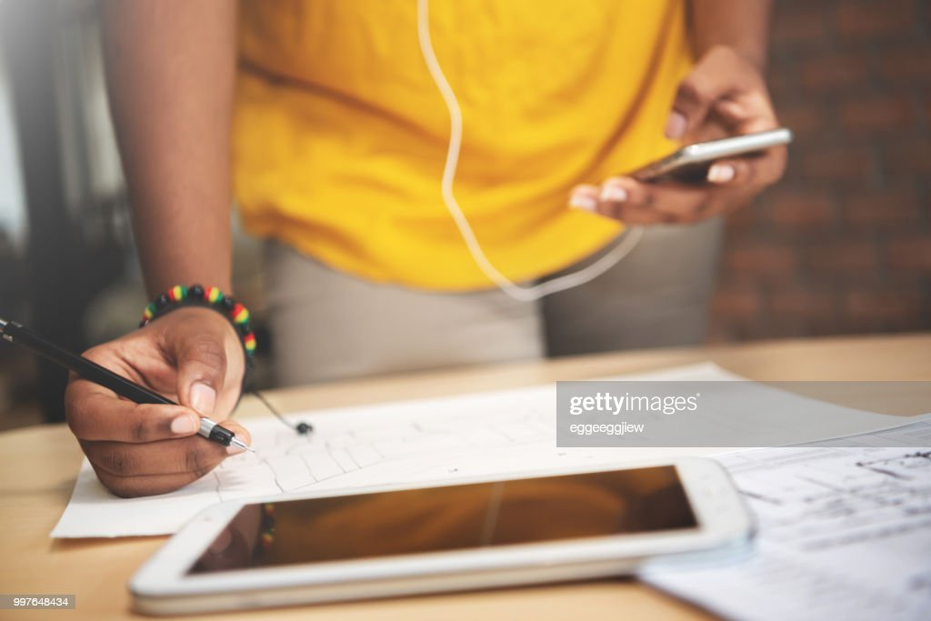 African designer in yellow shirt is working with sketching drawing. : Stock Photo