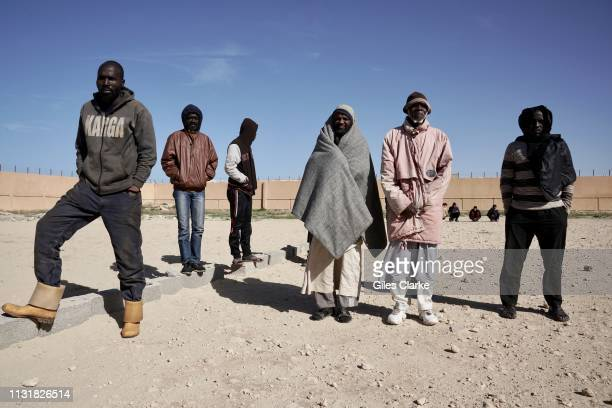 African detainees wait in line in the compound before the daily morning roll call at Qanfoodah Detention Center on February 2, 2019 in Libya. At the...