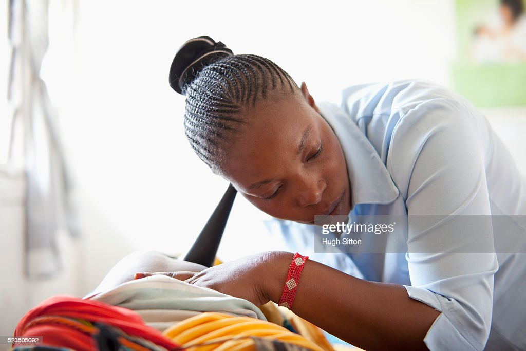 African doctor examining pregnant woman : Stock Photo