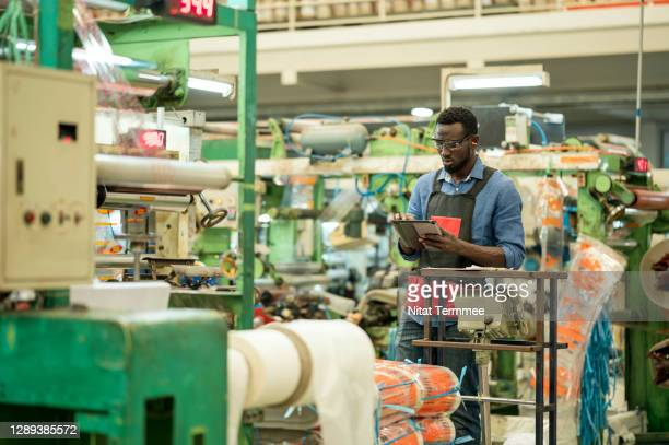 african engineer using digital tablet while working on production line in plastic factory. - manufacturing stock pictures, royalty-free photos & images