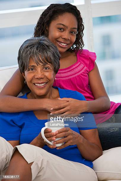 African ethnicity granddaughter hugging grandmother