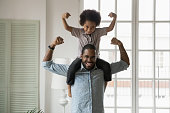 African ethnicity little son sitting on fathers shoulders showing biceps
