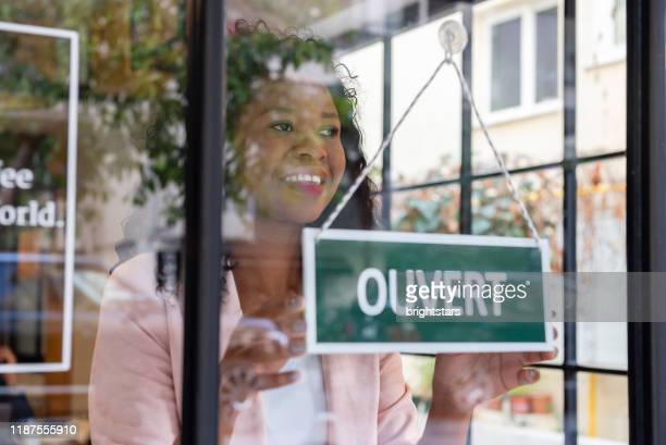 african ethnicity woman opening the store - french culture stock pictures, royalty-free photos & images