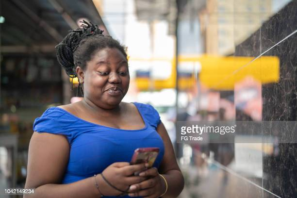 african ethnicity woman using mobile - ugly black women stock photos and pictures