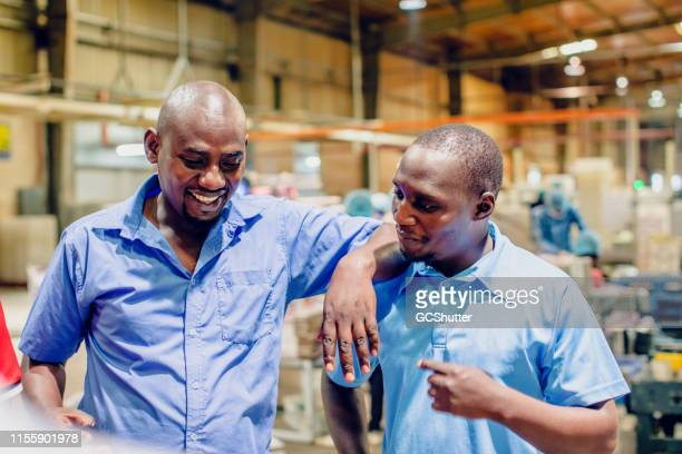 african factory supervisor casually chatting during their break - trade union stock pictures, royalty-free photos & images