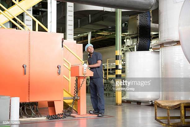Africano fábrica trabajador funcionamiento de maquinaria en una lata de aluminio instalaciones de producción