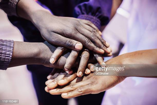 african factory workers joining hands to showcase unity - may day international workers day stock pictures, royalty-free photos & images