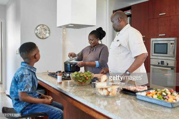 african family in kitchen during midday meal preparation - chubby granny stock pictures, royalty-free photos & images