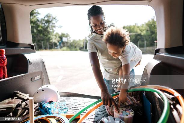 african family unpacking stuffs out of car trunk - black boot stock pictures, royalty-free photos & images