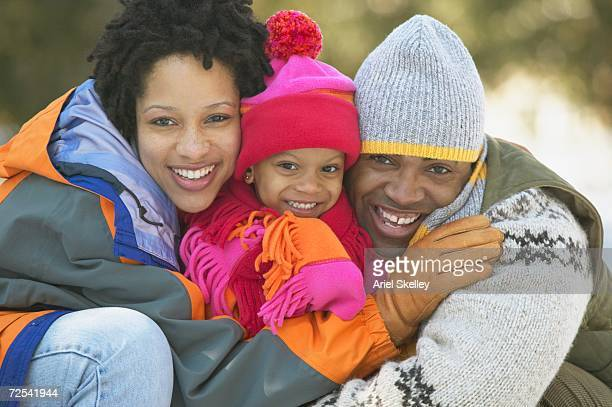 African family wearing winter clothes and hugging