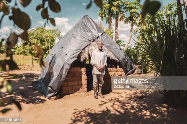 afrikanischer farmer steht vor seiner grasshütte - afrikanischer volksstamm stock-fotos und bilder