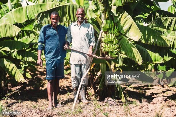 彼の息子が彼らのバナナファームに立っているアフリカの農夫 - ザンビア ストックフォトと画像