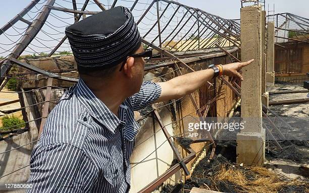 African fashion designer Alphadi looks at the damage caused by a fire at his workshops in Niamey on October 2 2011 Fashion designer Alphadi who comes...