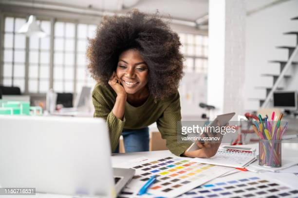 african fashion designer working in studio and using laptop and smart phone - paleta de cores imagens e fotografias de stock