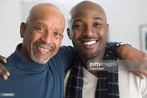 African father and adult son hugging