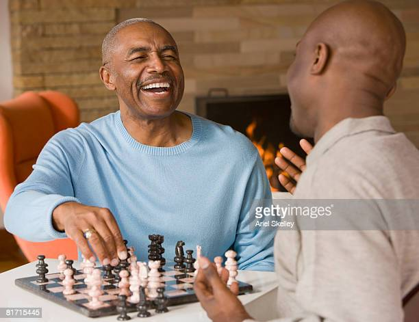 african father and adult son playing chess - playing chess stock pictures, royalty-free photos & images