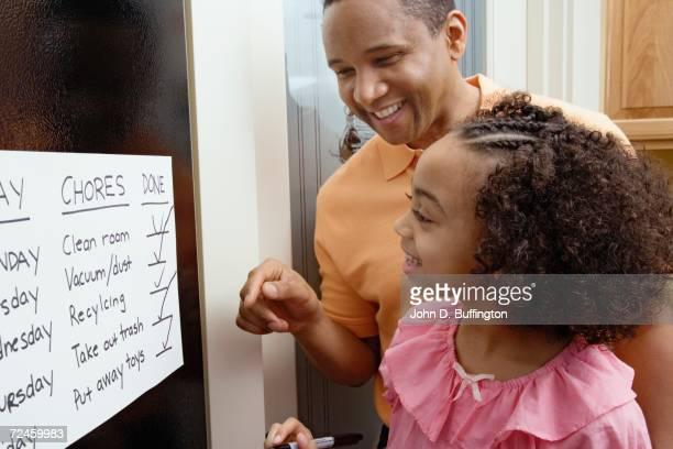 african father and daughter looking at chores chart - haushaltsaufgabe stock-fotos und bilder