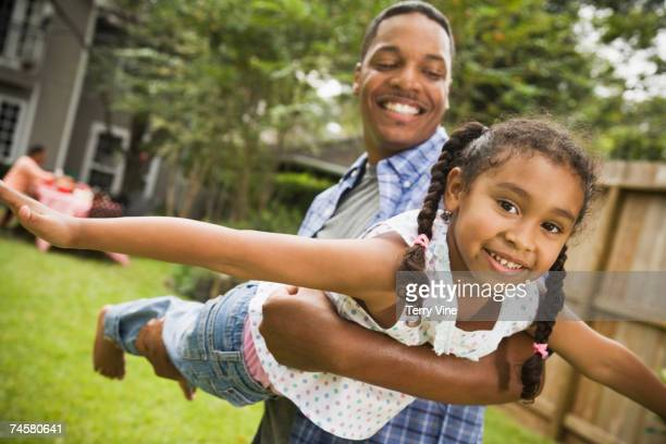 African father and daughter playing outdoors