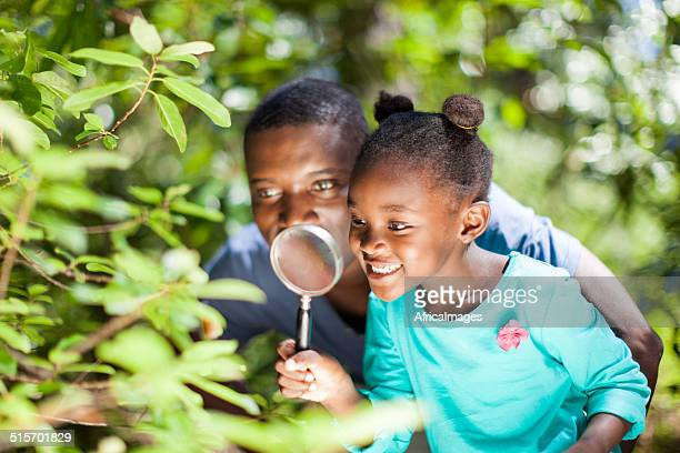 African father and daughter using a magnifying glass