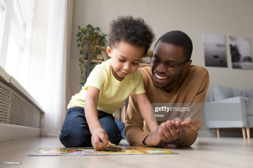 African father and little son collect jigsaw puzzle at home : Stock Photo