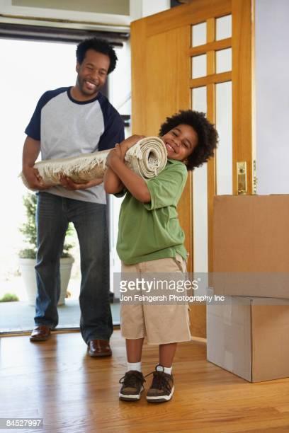 african father and son carrying carpet into new home - oggetti pesanti foto e immagini stock