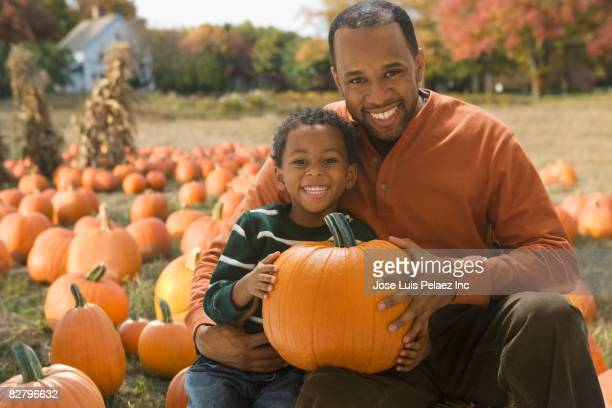 african father and son holding pumpkin at pumpkin patch - pumpkin patch stock photos and pictures
