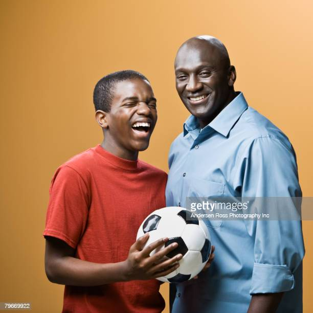 African father and son holding soccer ball