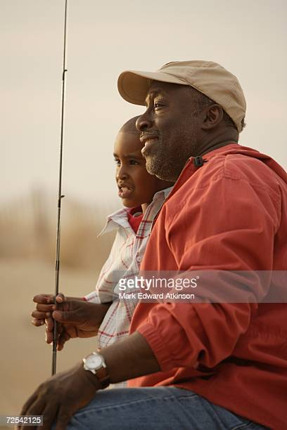 African father and son on beach with fishing gear
