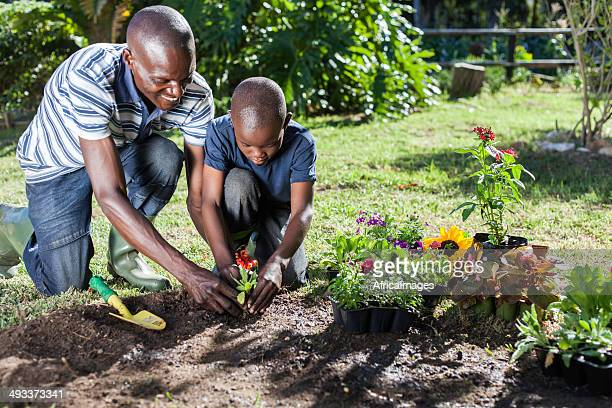 African father and son plant flowers together