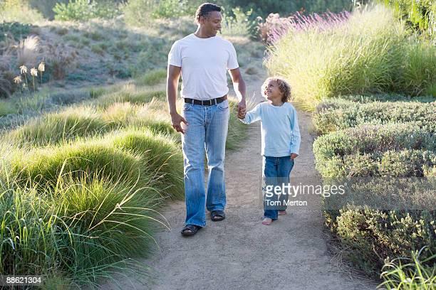 African père et fils à pied dans le jardin