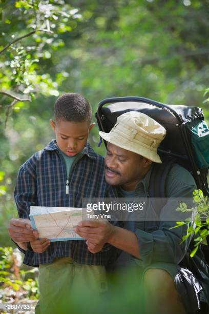 African father and son with map in woods