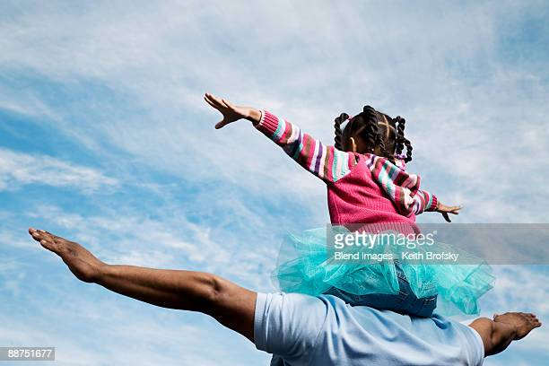 african father carrying daughter on shoulders - carrying on shoulders stock pictures, royalty-free photos & images