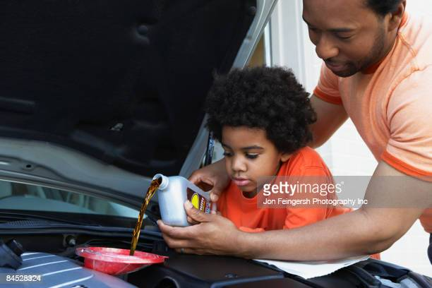african father helping son pour oil into car engine - motor oil stock pictures, royalty-free photos & images