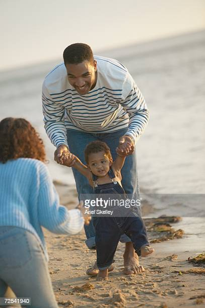 african father helping toddler walk to mother at beach - 初めての出来事 ストックフォトと画像