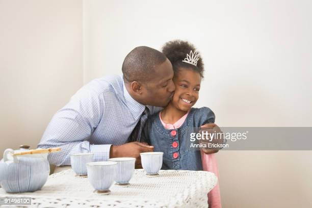 African father kissing daughter with tiara