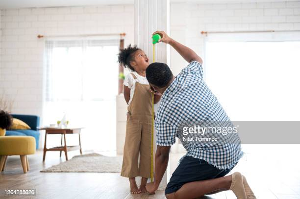 a african father measuring his daughter height against a house pillar in living room. - high scale magnification stock pictures, royalty-free photos & images